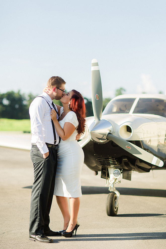 Engaged couple kissing in front of aircraft | Vintage Airport Engagement | Ailyn La Torre Photography