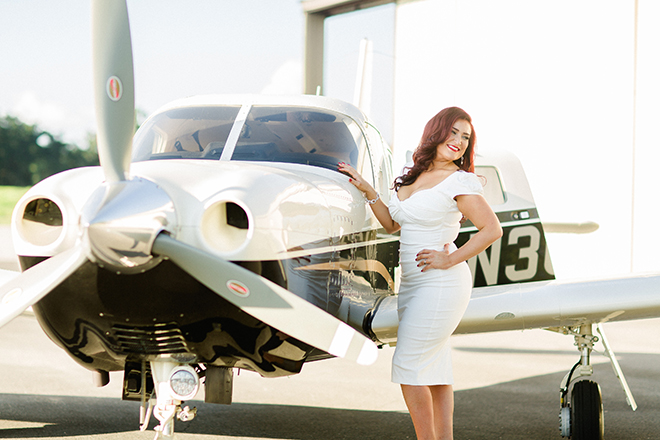 Glamourous woman standing by propeller plane | Vintage Airport Engagement | Ailyn La Torre Photography