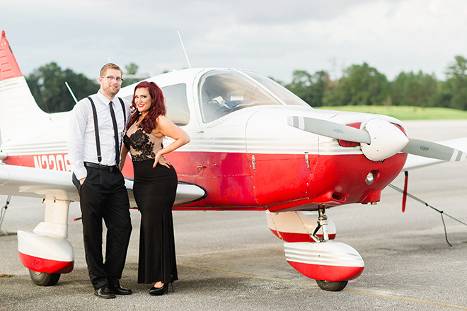Engaged couple standing beside red plane | Vintage Airport Engagement | Ailyn La Torre Photography