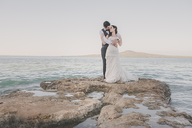 Wedding couple standing on rocks | Rose Garden Beach Wedding | Levien and Lens Photography