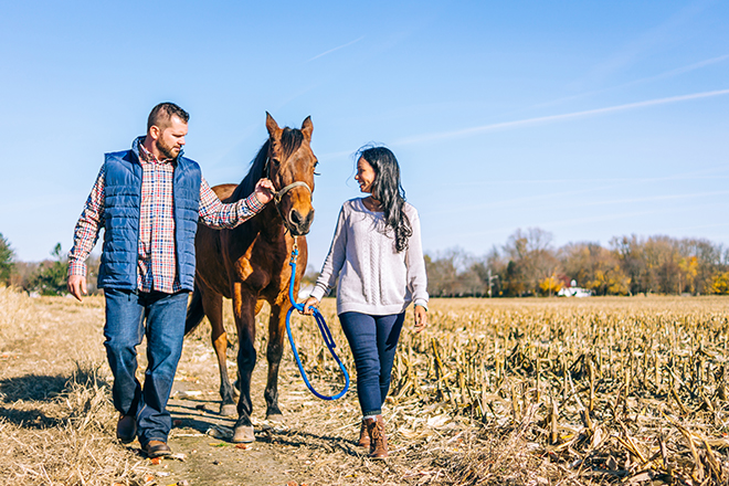 Man and woman walking through field with horse | Rustic Engagement | Anders Portfolio Photography