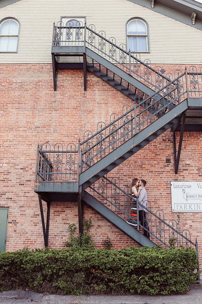 Engaged couple standing on fire escape | Modern Country Engagement | Brandy Swartz Photography