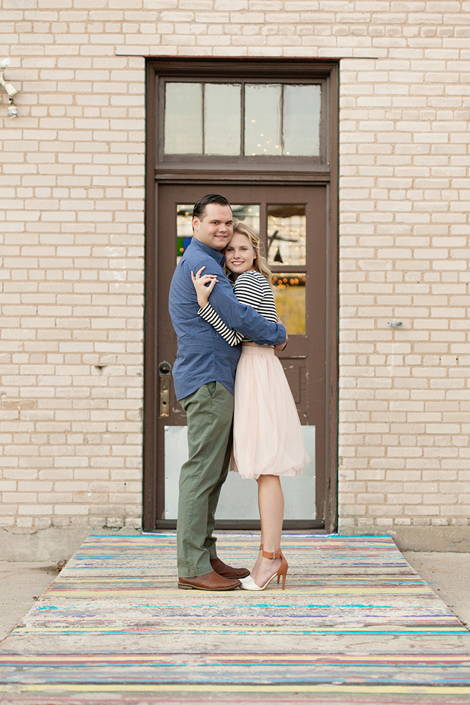 Couple standing beside door | Michigan Fall Engagement | The MittenTog