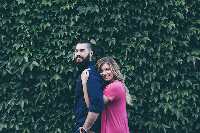 Couple standing infront of ivy | Sweet and Sassy Downtown Engagement | Brandy Swartz