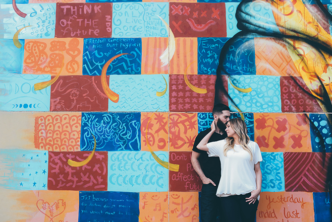 Couple standing beside colourful wall | Sweet and Sassy Downtown Engagement | Brandy Swartz