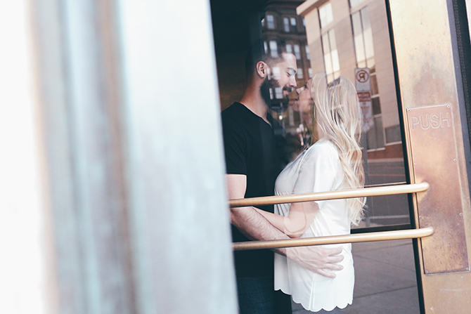 Kissing in the doorway | Sweet and Sassy Downtown Engagement | Brandy Swartz