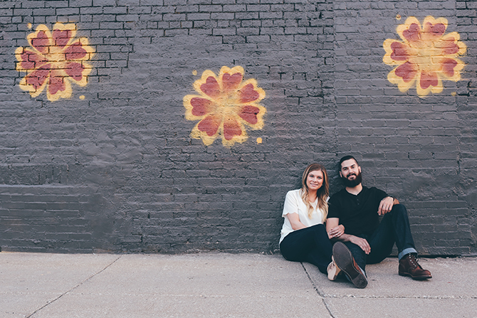 Man and Woman sitting beside wall | Sweet and Sassy Downtown Engagement | Brandy Swartz