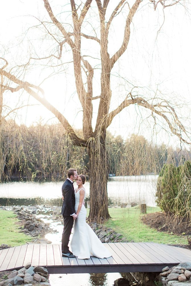 Newlyweds in love on bridge | Lake Side Wedding | Krystal Balzer Photography