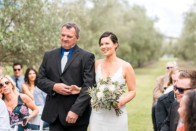 Bride walking down aisle | Olive Tree Vineyard Wedding Raquelle Loraine Photography
