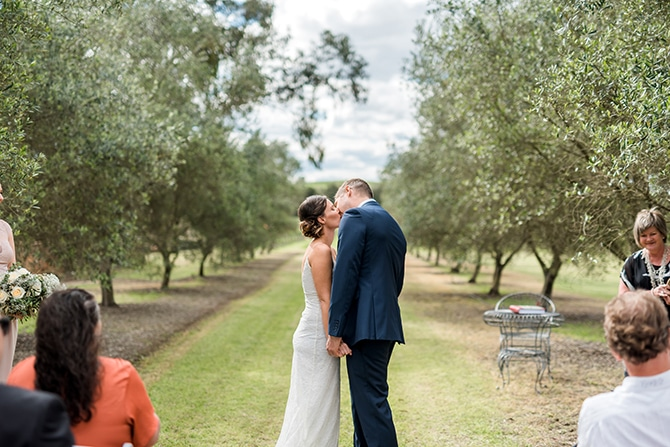 Couple kissing at ceremony | Olive Tree Vineyard Wedding Raquelle Loraine Photography