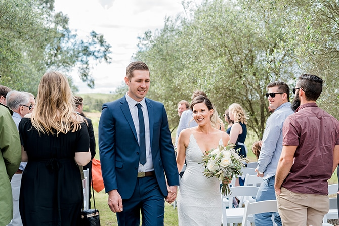 Newlyweds walking down aisle | Olive Tree Vineyard Wedding Raquelle Loraine Photography