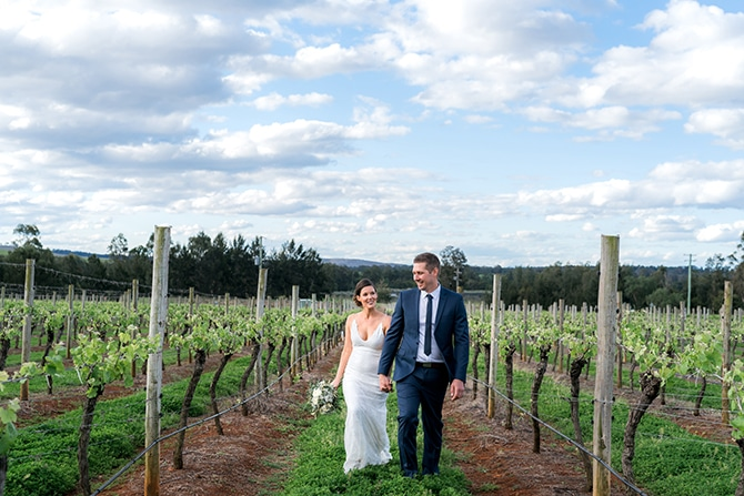 Newlyweds walking through vineyard | Olive Tree Vineyard Wedding Raquelle Loraine Photography