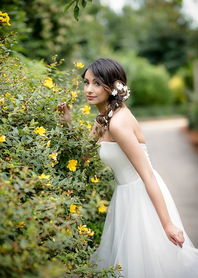 Bride smelling flowers in English garden | Contemporary Summer Bridal Inspiration