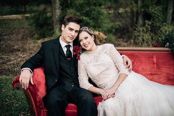 Couple sitting on red sofa | Intimate Winter Chapel Wedding | Rebecca Chesney Photo