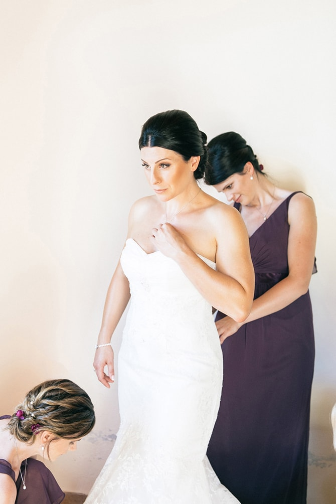Bride putting on wedding dress | Natural Alfresco Wedding in Crete HannaMonika Photography