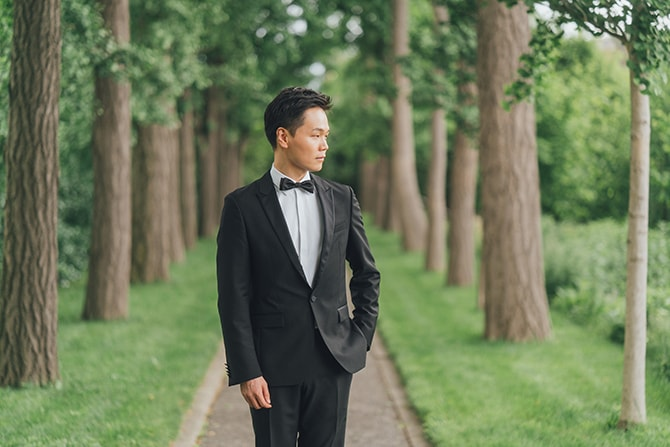 Groom standing on a path of trees