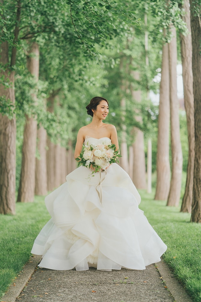 Bride standing on path of trees