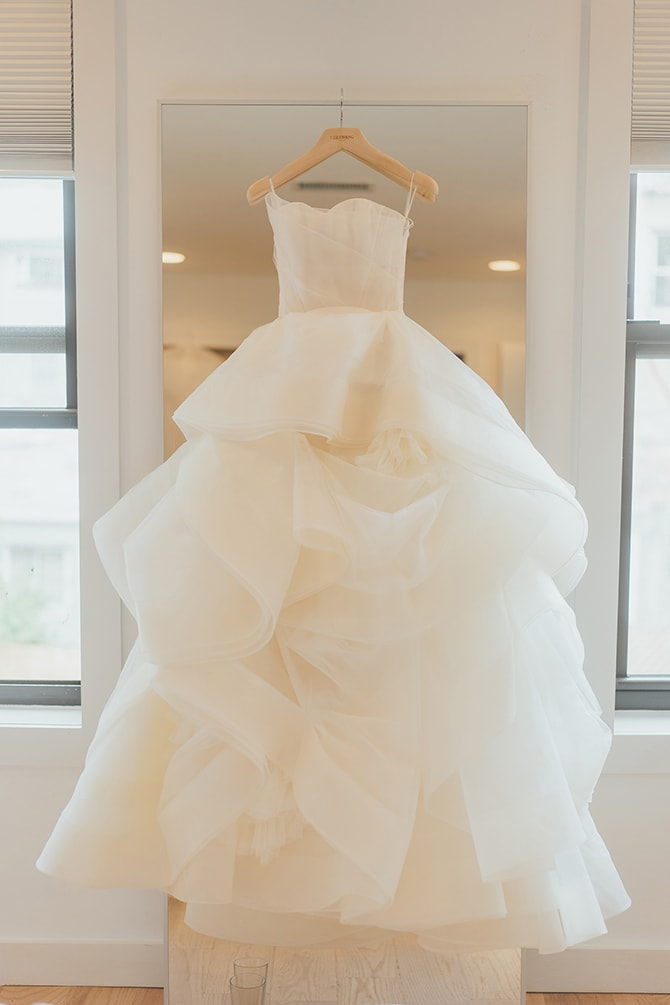 White wedding dress hanging from mirror