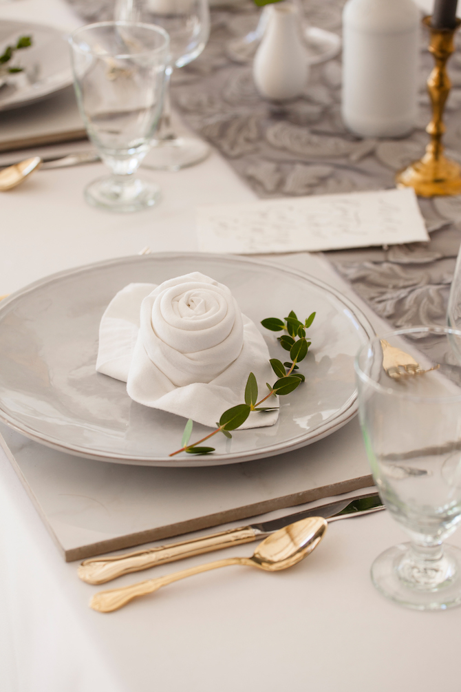 Grey dinnerware with gold cutlery at wedding