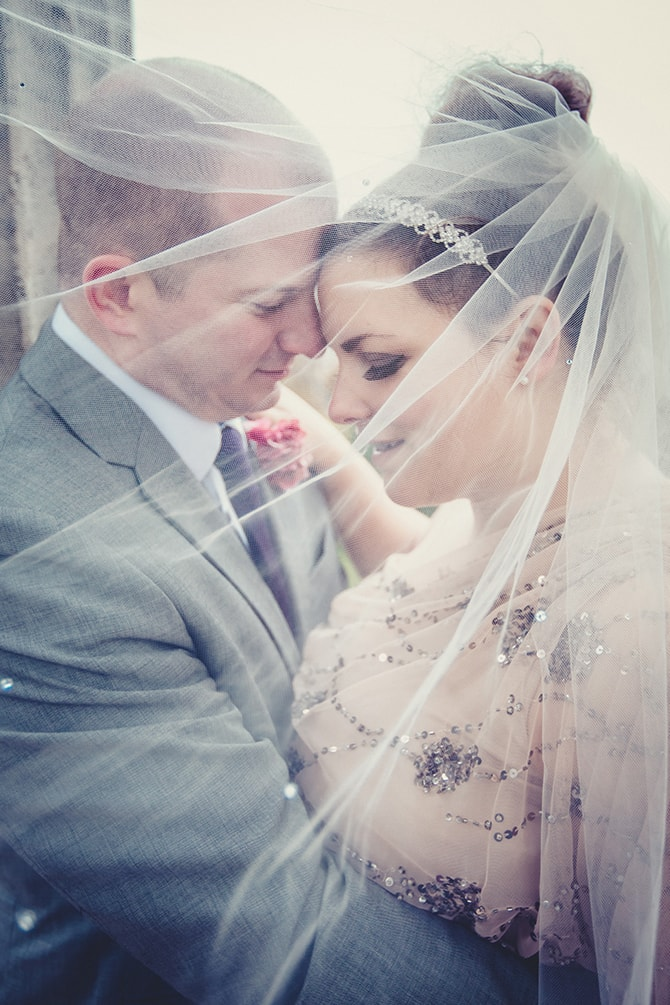 Bride and Groom under beautiful veil