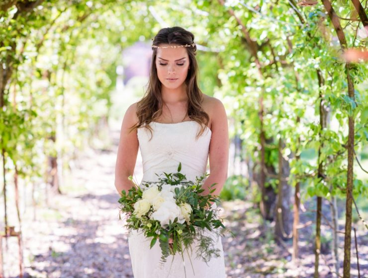 Bride walking through tunnel of plants