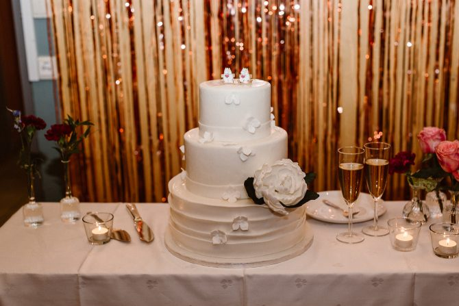 3-tiered white wedding cake in front of gold backdrop | Real Wedding Mari and Tarjei at Båtsportens Hus