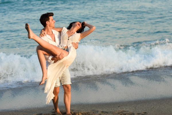 Young happy couple walking in a beautiful beach. Funny Man carrying a woman on his arms. People wearing casual clothes.